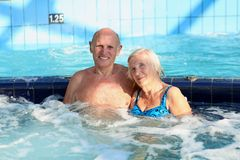 Active senior couple enjoying jacuzzi. Happy healthy senior couple having fun together in the swimming pool enjoying jacuzzi Stock Photo