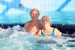 Active senior couple enjoying jacuzzi. Happy healthy senior couple having fun together in the swimming pool enjoying jacuzzi Stock Photos