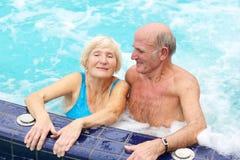 Active senior couple enjoying jacuzzi. Happy healthy senior couple having fun together in the swimming pool enjoying jacuzzi Royalty Free Stock Photography
