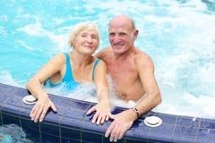 Active senior couple enjoying jacuzzi. Happy healthy senior couple having fun together in the swimming pool enjoying jacuzzi Royalty Free Stock Photos