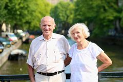 Active senior couple enjoying trip to Amsterdam. Happy senior caucasian couple travelling around Europe walking in the streets of Amsterdam, enjoying scenes of stock photography
