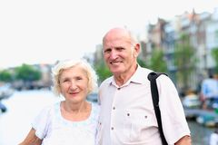 Active senior couple enjoying trip to Amsterdam. Happy senior caucasian couple travelling around Europe walking in the streets of Amsterdam, enjoying scenes of stock photography