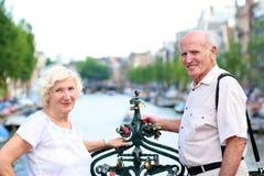 Active senior couple enjoying trip to Amsterdam. Happy senior caucasian couple travelling around Europe walking in the streets of Amsterdam, enjoying scenes of royalty free stock photos