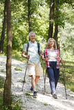 Active senior couple. Full length portrait of senior couple enjoying a nordic walk. Active elderly women and men walking on the forest and smiling Stock Photography