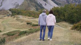 Active senior couple hiking in mountains, enjoying their adventure