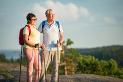 Active senior couple hiking on the top of rock. Exploring. Mature men and women Happily smiling. Nordic walking, trekking. Scenic view of gulf and sea. Healthy Royalty Free Stock Photos