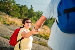Active senior couple hiking on the top of rock Stock Photos