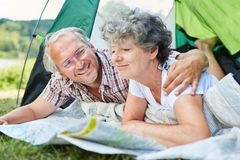 Active senior couple with map in tent. At camping. Holiday in nature in summer royalty free stock photography