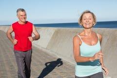 Active senior couple out for a jog. On a sunny day Stock Photos