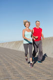 Active senior couple out for a jog. On a sunny day Stock Photo