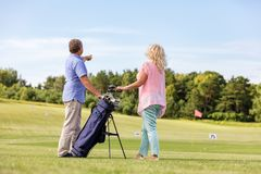 Active senior couple playing golf on a course. stock photo