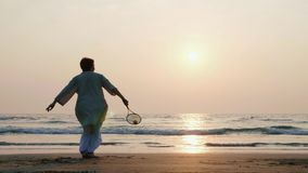 Active senior couple playing tai chi ballon ball at the beach in slow motion.