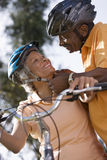 Active senior couple preparing to cycle in park, man adjusting woman's cycling helmet strap, smiling, close-up, low angle view (ti Stock Images