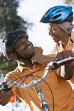 Active senior couple preparing to cycle in park, woman adjusting man's cycling helmet strap, smiling, close-up, low angle view (ti Stock Image