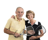 Active senior couple ready for sport. Studio shot of happy senior couple holding rackets on white background royalty free stock photography