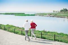 Active Senior Couple Running Along Lake. Back view portrait of active senior couple running together in park along lake, copy space stock photography