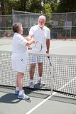 Active Senior Couple - Sportsmanship. Active senior couple shakes hands over the tennis net stock photos