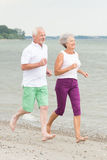 Active senior couple. Active and sporty senior couple at the beach royalty free stock photo
