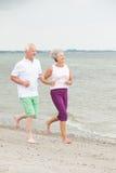 Active senior couple. Active and sporty senior couple at the beach stock photos