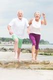 Active senior couple. Active and sporty senior couple at the beach stock photo