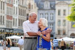 Active senior couple traveling in Europe. Happy senior couple, men and wife, traveling around Europe, enjoying beautiful old square in city of Leuven, Belgium royalty free stock photo