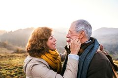 Senior couple on a walk in an autumn nature. Active senior couple on a walk in a beautiful autumn nature, making funny faces Stock Photo