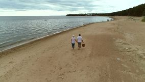 Active senior couple walking through beach together. stock footage