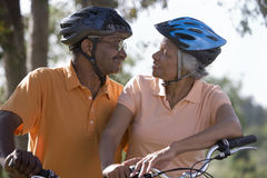 Active senior couple wearing cycling helmets and polo shirts, sitting on bicycles in park, face to face, smiling Stock Photo