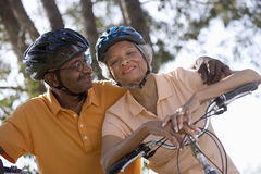 Active senior couple wearing cycling helmets and polo shirts, sitting on bicycles in park, man embracing woman, smiling, portrait, Stock Image