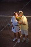 Active senior couple win. Active senior couple is posing on the tennis court with tennis racket and cup in hand. Outdoor, sunlight royalty free stock photos