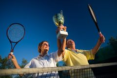 Active senior couple win. Active senior couple is posing on the tennis court with tennis racket and cup in hand. Outdoor, sunlight stock photos