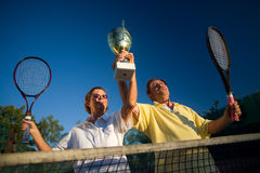 Active senior couple win. Active senior couple is posing on the tennis court with tennis racket and cup in hand. Outdoor, sunlight Royalty Free Stock Images
