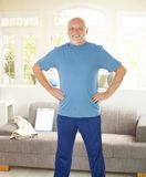 Active senior doing exercises. At home in living room, smiling Royalty Free Stock Photo