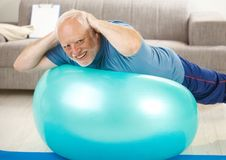Active senior doing exercises on gym ball. At home, hands on nape, smiling at camera Royalty Free Stock Photography