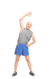 Active senior doing stretching exercises. Full length portrait of an active senior doing stretching exercises and looking at the camera isolated on white stock photos