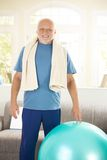 Active senior exercising with fit ball. At home, smiling at camera stock image