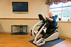 Active Senior Exercising in Gym. Senior male (knee replacemant surgery patient) sitting on a recumbent stepper in a rehab gym. Horizontal. Copy space Stock Photos