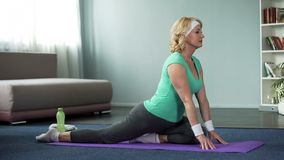 Active senior female practicing yoga on mat at home, healthy lifestyle, wellness. Stock photo royalty free stock photography