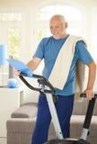Active senior with fitness equipment. Active senior in sportswear with fitness equipment, looking at clipboard, smiling royalty free stock image