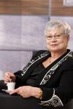 Active senior lady having coffee Stock Images