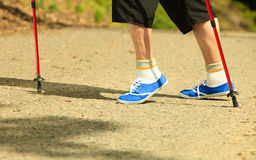 Active senior legs in sneakers nordic walking in a park. Royalty Free Stock Images