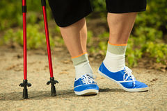 Active senior legs in sneakers nordic walking in a park. Royalty Free Stock Image