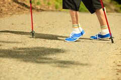 Active senior legs in sneakers nordic walking in a park. Stock Photography