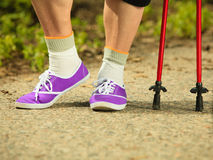 Active senior legs in sneakers nordic walking in a park. Stock Image