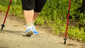 Active senior legs in sneakers nordic walking in a park. Stock Photo
