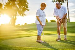 Active senior lifestyle, elderly couple playing golf together. At sunset stock images