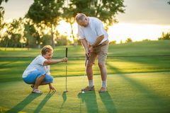 Active senior lifestyle, elderly couple playing golf together. At sunset royalty free stock photos