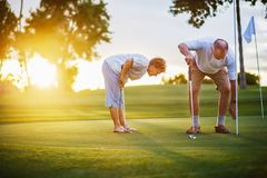 Active senior lifestyle, elderly couple playing golf together at sunset. At golf course stock image