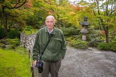 Active Senior Male Photographer. An elderly man wearing a camera on a walking path in a Japanese garden with early fall foliage royalty free stock photo