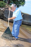 Senior raking debris from the sand Royalty Free Stock Photos